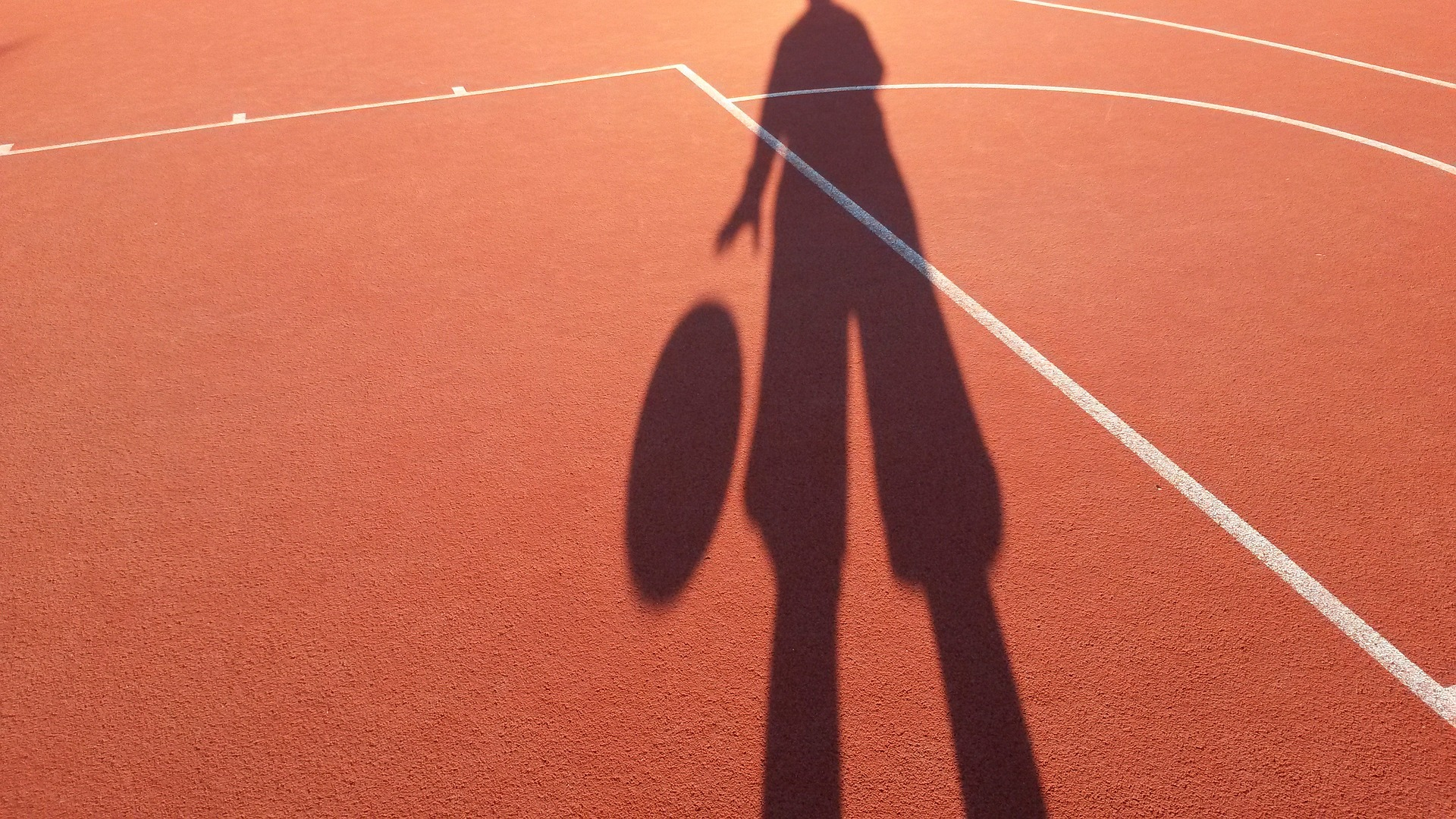 The Man Defined - basketball player shadow on outdoor court